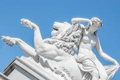 Mujer sensual de la era del renacimiento de la estatua antigua que pone en el león grande en Potsdam, Alemania imagen de archivo