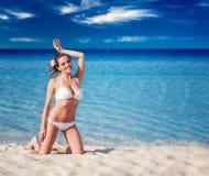 Mujer sensual en el bikini blanco que se sienta en la playa imagen de archivo libre de regalías