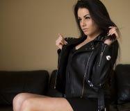 Mujer sensual en la sentada negra de la chaqueta de cuero Foto de archivo libre de regalías