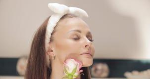 Mujer sensual en la venda que huele el brote color de rosa almacen de metraje de vídeo