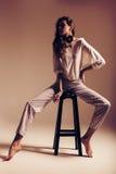 Mujer sensual en los pantalones rayados que se sientan en silla Imágenes de archivo libres de regalías