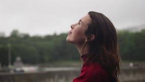 Mujer sensual feliz joven que mira para arriba la lluvia, sonriendo y frotando ligeramente la cabeza almacen de video