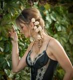 Mujer sensual hermosa con las rosas en el pelo que presenta cerca de una pared de hojas verdes Hembra joven en vestido elegante n Fotografía de archivo libre de regalías