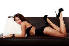 Mujer sensual hermosa que se sienta en un sofá Fotos de archivo libres de regalías