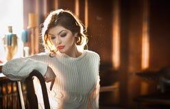 Mujer sensual joven que se sienta con la ventana en fondo Muchacha hermosa con la blusa cómoda blanca que sueña despierto dentro, Foto de archivo