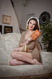 Mujer sensual joven que se sienta en el sofá que lleva a cabo una máscara Muchacha larga hermosa del pelo con ropa cómoda que sue Imagen de archivo libre de regalías