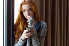 Mujer sensual joven que toca sus labios y que usa smartphone Fotos de archivo