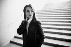 Mujer sensual que se coloca solamente en las escaleras subterráneos en negro y Imagen de archivo