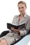 Mujer sentada tomando notas Imagen de archivo