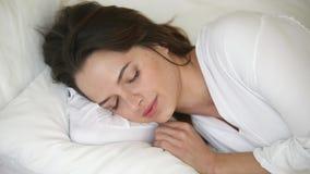 Mujer serena que miente en la almohada suave en la cama que duerme bien metrajes