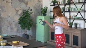 Mujer seria atractiva con el pelo del jengibre que sostiene el vino del vidrio y que charla en el teléfono, bailando en cocina co almacen de video