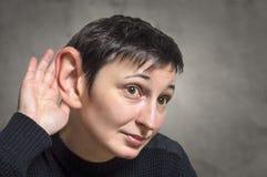 Mujer seria con un oído grande que escucha atento fotografía de archivo libre de regalías