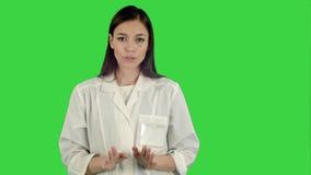 Mujer seria en capa del laboratorio que habla con la cámara en una pantalla verde, llave de la croma almacen de metraje de vídeo