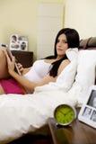 Mujer seria en tablilla de la lectura de la cama Imagenes de archivo
