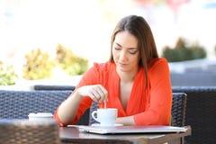 Mujer seria en una cafeter?a que revuelve la bebida imagen de archivo