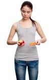 Mujer seria joven que sostiene una píldora en una mano y una manzana en t Imagenes de archivo
