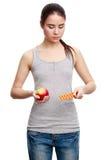 Mujer seria joven que sostiene una píldora en una mano y una manzana en t Fotos de archivo libres de regalías