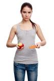 Mujer seria joven que sostiene una píldora en una mano y una manzana en t Imagen de archivo