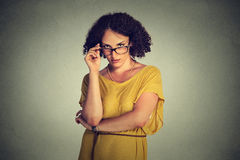 Mujer seria malintencionada enojada con los vidrios en el vestido amarillo que le mira escéptico Foto de archivo