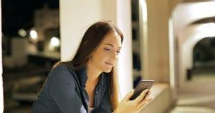 Mujer seria que busca en el teléfono elegante en la noche almacen de video