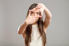Mujer seria que crea un marco con los fingeres Imagen de archivo libre de regalías