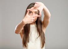 Mujer seria que crea un marco con los fingeres Imagen de archivo