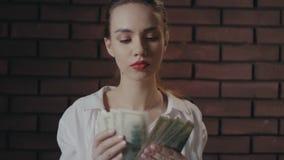 Mujer seria que cuenta billetes de banco del dinero en la pared de ladrillo Empresaria rica almacen de video