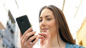 Mujer seria que hojea el contenido elegante en línea del teléfono metrajes