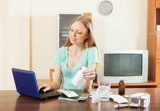 Mujer seria que lee sobre medicaciones en Internet Imágenes de archivo libres de regalías