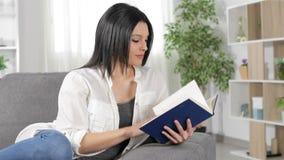 Mujer seria que lee un libro en casa almacen de video