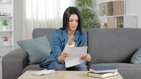 Mujer seria que lee una letra en casa almacen de video