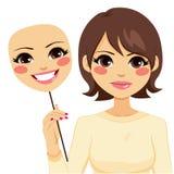 Mujer seria que lleva a cabo la máscara feliz Imagenes de archivo