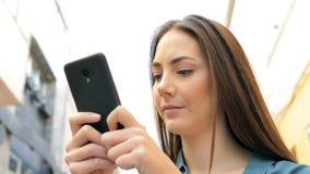 Mujer seria que manda un SMS en el teléfono que se coloca en la calle