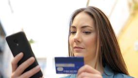 Mujer seria que paga con la tarjeta de crédito en línea almacen de metraje de vídeo