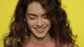 Mujer seria que ríe en la cámara lenta Muchacha de risa que mira in camera en amarillo almacen de metraje de vídeo