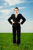 Mujer seria que se coloca en el campo verde Fotografía de archivo libre de regalías