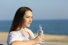 Mujer seria que sostiene una botella de agua en la playa Imagenes de archivo