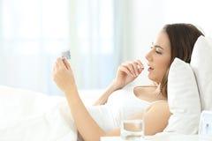 Mujer seria que toma una píldora anticonceptiva en la cama Imágenes de archivo libres de regalías