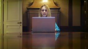 Mujer seria que trabaja en el ordenador portátil que se sienta en la tabla en el estudio casero almacen de metraje de vídeo
