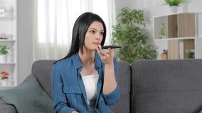 Mujer seria que usa el reconocimiento vocal del teléfono almacen de metraje de vídeo