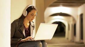 Mujer seria que usa un ordenador portátil con los auriculares en la noche almacen de video