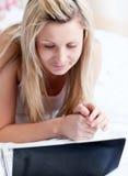 Mujer seria que usa una computadora portátil que miente en una cama Imágenes de archivo libres de regalías