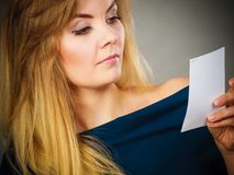 Mujer seriamente preocupante que mira el trozo de papel fotografía de archivo libre de regalías