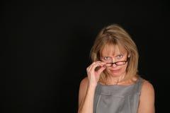 Mujer severa que mira sobre los vidrios Imagen de archivo libre de regalías