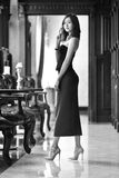 Mujer sexual joven asiática de la foto blanca negra con el pelo largo un vestido de noche negro que presenta por una ventana Foto de archivo