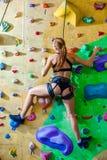 Mujer sexual que sube en una pared en un centro que sube al aire libre Imágenes de archivo libres de regalías