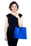 Mujer shopaholic joven que lleva el bolso brillante Foto de archivo