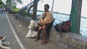 Mujer sin hogar que abraza un perro en el agua de la rotura del lago almacen de metraje de vídeo