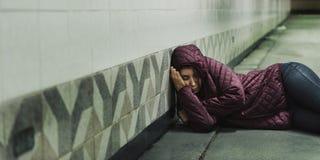 Mujer sin hogar que duerme en el piso fotos de archivo
