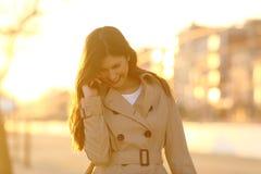Mujer sincera que habla en el teléfono en la puesta del sol fotos de archivo libres de regalías